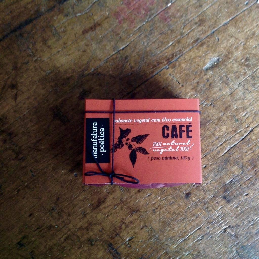 Embalagem Manufatura Poética com texto: sabonete artesanal de café, 100% vegetal e natural, e silhueta de galho e folhas de café