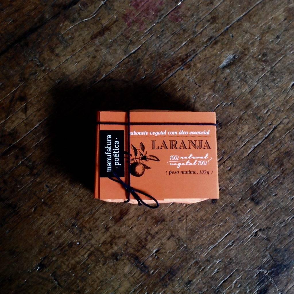 Embalagem Manufatura Poética com texto: sabonete artesanal de laranja, 100% vegetal e natural e silhueta de galho de laranjeira