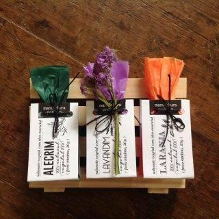 3 mini-sabonetes embalados, sobre pallet de madeira sobre mesa de madeira